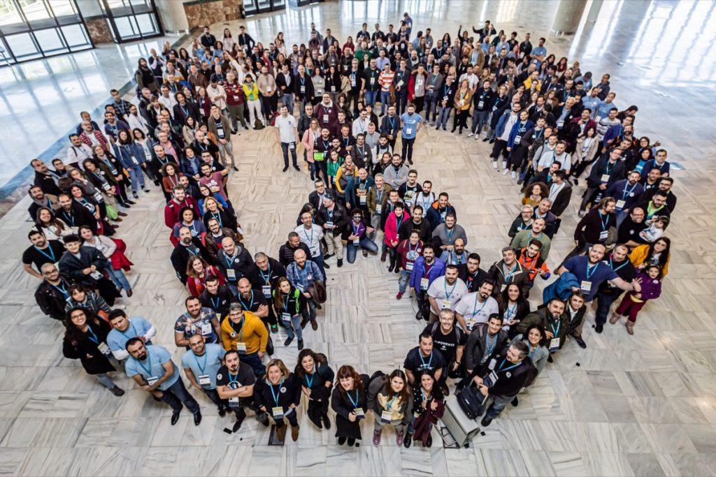 asistentes a una WordCamp forman el logo de WordPress visto desde arriba
